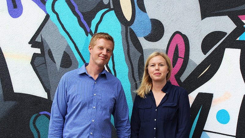The owners of BY DYB, Kaseper and Sofie, on a background of graffiti.