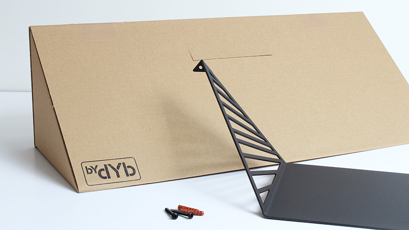 Cardboardbox with logo and shelf from BY DYB, screws and rawlplugs to hang the shelf.