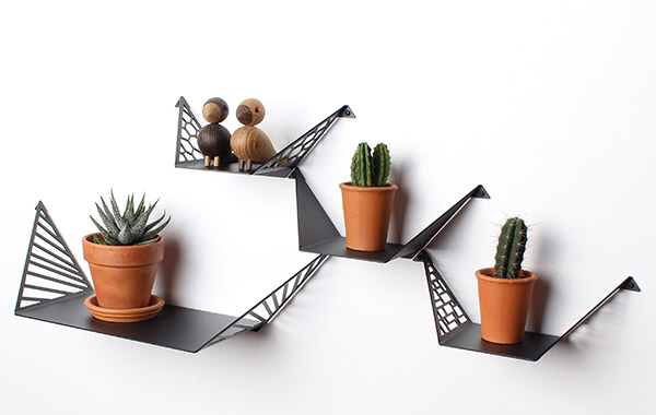 three small shelves and one large shelf from By Dyb styled with cacti in brown flowerpots and wooden Kay Bojesen Love Birds.