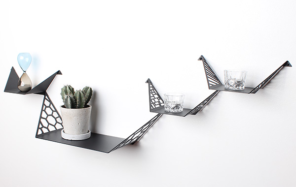 three small shelves and one large shelf from By Dyb styled with candleholders, hourglass and cactus in gray flowerpot