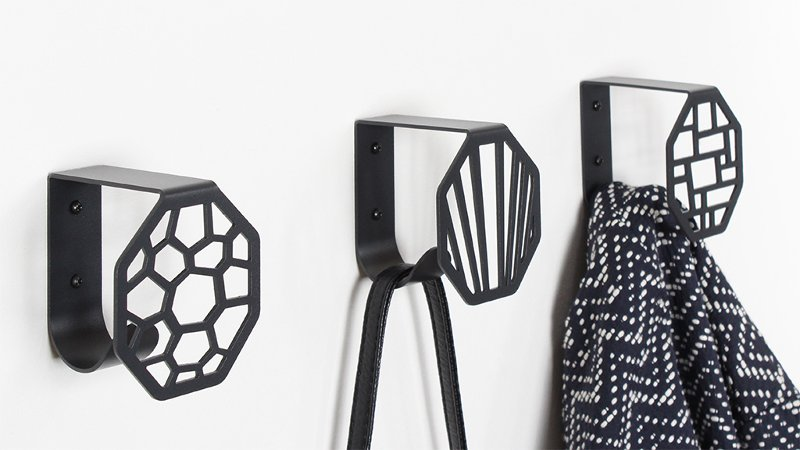 Three KNAGEN wall hooks from BY DYB in a straight line in Hex, Line, and Square pattern