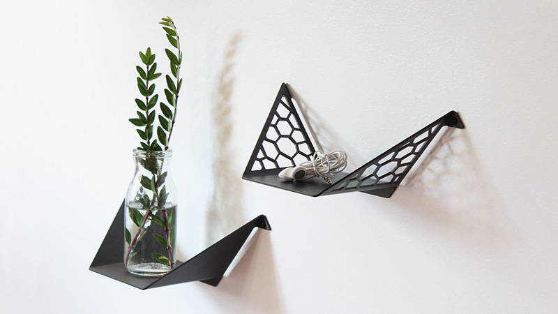 Small clean shelf and small hex shelf from BY DYB styled with green branches in a vase and earphones