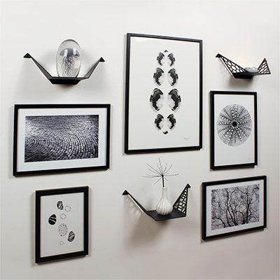 Gallery wall with small sheles from BY DYB, pictures in black and white, shelves styled with candle, little vase and glass jellyfish